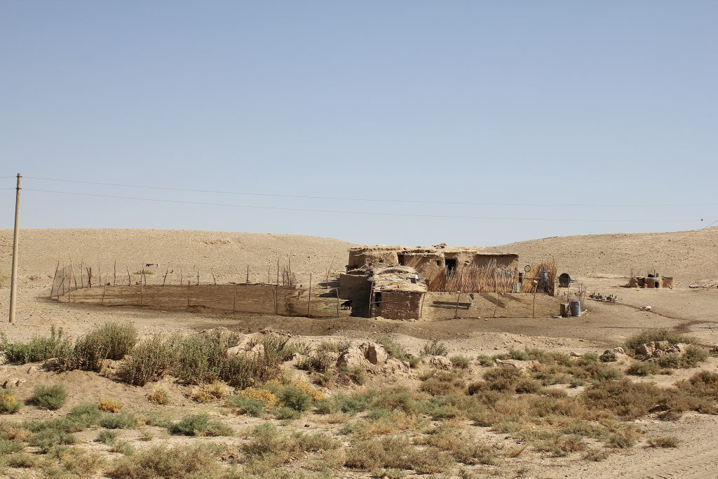 A building in an arid, environment, with some scrubby plants in the foreground